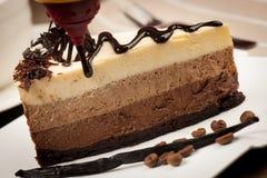 Köstliche Scheibe des Schokoladenkuchens mit Sirup- und Vanilleanschlägen Stockfotografie