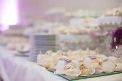 Köstliche u. geschmackvolle weiße verzierte kleine Kuchen am Hochzeitsempfang Stockbilder