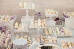 Köstliche u. geschmackvolle weiße verzierte kleine Kuchen am Hochzeitsempfang Stockfotos