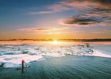 Kształtująca teren, Piękna lodowiec laguna w zmierzchu z faceta paddle abordażem, Zdjęcie Royalty Free