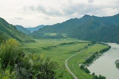 Kształtuje teren z gór drzewami i rzeką Zdjęcie Royalty Free