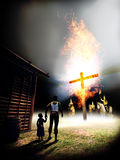 Ku Klux klan. Members of the Ku Klux Klan burning a cross close to the house of an African American citizen with his young daughter vector illustration