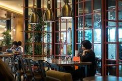 Kuala Lumpur, circa 2016 - Asiatsmänner und -frauen, die Kaffee herein trinken Stockbild