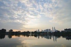 Kuala Lumpur City med reflexion på sjön och det dramatiska molnet Arkivbilder