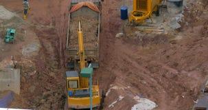 In Kuala Lumpur gießt Malaysia im Grubenbagger Erde in einen LKW stock video footage