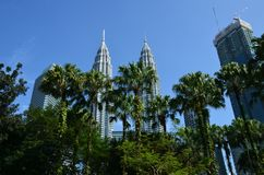 Kuala Lumpur, Malásia - 23 de abril de 2017: Opinião do dia das torres gêmeas de Petronas e das construções vizinhas em Kuala Lum fotos de stock