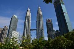 Kuala Lumpur, Malásia - 23 de abril de 2017: Opinião do dia das torres gêmeas de Petronas e das construções vizinhas em Kuala Lum foto de stock royalty free