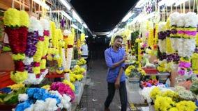 Kuala Lumpur, Malásia - 17 de julho de 2018: Andar entre o mercado está com as festões coloridas surpreendentes da flor no mercad video estoque