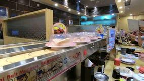 Kuala Lumpur, Malásia - 18 de julho de 2018: Sushi da correia transportadora ou sushi de giro em um rei Restaurant do sushi vídeos de arquivo