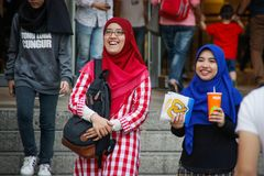 Two young girls in bright hijabs are walking and laughing near the Petronas Towers stock photography