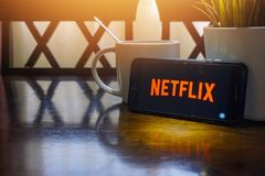 Smartphone displaying word Netflix on wooden table with selective focus and crop fragment Stock Photo