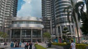 KUALA LUMPUR MALAYSIA - mars 9, 2018: Turists som framme promenerar gränden av de Petronas tvillingbröderna stock video