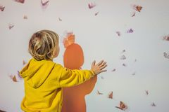 Kuala Lumpur, Malaysia November 20, 18: The boy catches electronic butterflies on the wall stock photography
