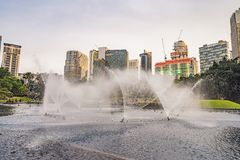 Kuala Lumpur, Malaysia, November 18, 2018: Fountain on the lake in the evening, near by Twin Towers with city on