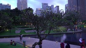 Petronas Twin Towers Symphony Lake, with local and tourist enjoying the fountain show. Kuala Lumpur, Malaysia - October 27, 2018: Establishing b-roll cinematic stock video