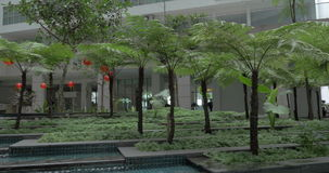 In Kuala Lumpur, Malaysia seen building and unusual fountain. With trees, palms and orange lanterns stock footage