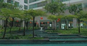 In Kuala Lumpur, Malaysia seen skyscraper and unusual fountain. With trees and orange lanterns stock video