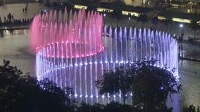 Kuala Lumpur, Maleisië 12 Oktober, 2016: De fonteinen staken met kleurenlicht aan bij de tweelingtorens van Petronas in nacht Kua stock video