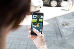 KUALA LUMPUR, MALEZJA, LIPIEC 16, 2016: IOS użytkownik bawić się Pokemon Zdjęcie Royalty Free