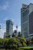 Kuala Lumpur Tower in betwen buildings and coconut trees Royalty Free Stock Photos
