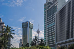 Kuala Lumpur Tower in betwen buildings and coconut trees Stock Photography