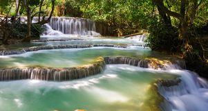 Waterfall in the forest. Kuang si waterfall in luang prabang, laos Jangle landscape with amazing turquoise water of Kuang Si cascade waterfall at deep tropical royalty free stock photography