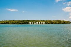Kuantan sign on river in Malaysia. River water and green coast on blue sky. Summer vacation. Discovery and adventure. Wanderlust and travelling concept stock photos