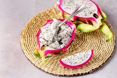 Kub av Dragon Fruit Served i halvan en Dragon Fruit på Straw Napkin Gray Background Tasty tropisk frukt Pitaya arkivfoto