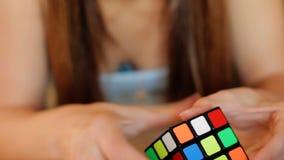 Kub för Rubik ` s Den härliga kvinnan spelar med en kub för Rubik ` s Flickan försöker att montera en kub för Rubik ` s kvinnaför arkivfilmer