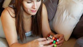 Kub för Rubik ` s Den härliga kvinnan spelar med en kub för Rubik ` s Flickan försöker att montera en kub för Rubik ` s kvinnaför stock video