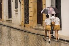 Kubańskie uczennicy chodzi z parasolowy Hawańskim Zdjęcie Royalty Free