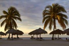 Kuba, 2014 Ein karibisches Strandurlaubsort mit Palmen, Schatten und Strandstühlen Lizenzfreies Stockfoto