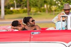 KUBA HAVANNACIGARR - MAJ 5, 2017: Afrikanska kvinnor i en cabriolet Närbild arkivfoto