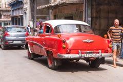 KUBA HAVANNACIGARR - MAJ 5, 2017: Röd amerikansk retro bil på stadsgatan Kopiera utrymme för text tillbaka sikt arkivbild