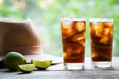 Kuba Libre koktajl z wapnem, lodem, mennicą, rumem na drewnianym stole z słomianym kapeluszem i widokiem taras, z bliska Obraz Stock
