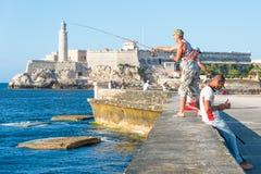 Kubaner som framme fiskar av den berömda slotten för El Morro i havannacigarr Arkivfoto