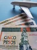 kubanische Banknoten, weißes Plastikflugzeug und blauer Hintergrund lizenzfreies stockbild