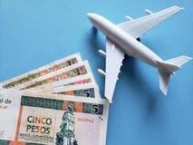 kubanische Banknoten, weißes Plastikflugzeug und blauer Hintergrund stockbilder