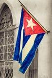 Kubanische Flagge auf einer verfallenden Nachbarschaft des Schmutzes Stockbild
