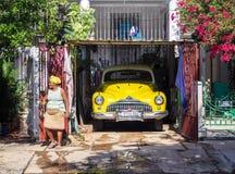 Kubanische Frauen mit gelbem Kopftuch nahe bei einem zusammenpassenden Auto Stockfoto