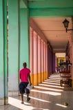 Kubanischer Mann, der durch buntes passway in Havana geht lizenzfreie stockfotografie