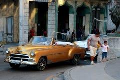 Kubanischer Mann, der einen großen goldenen Oldtimer in beschäftigter Havana-Straße fährt lizenzfreies stockfoto