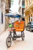 Kubansk taxicykel som framme parkeras av färgrika koloniala hus Arkivbild
