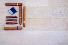 Kubanska cigarrer och en lighterr Arkivfoto
