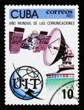 Kubaportostämpeln visar sputniken, den satellit- antennen, jordklotet och emblemet, år av kommunikationen, circa 1983 Royaltyfri Foto