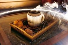 Kubek ciepła herbata z kawałkami manadarines na drewnianej tacy w dymu Obrazy Royalty Free