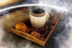 Kubek ciepła herbata z kawałkami manadarines na drewnianej tacy w dymu Obrazy Stock