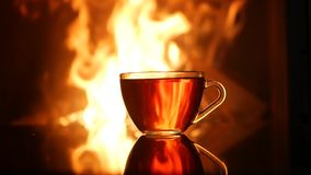 Kubek herbata na tle płonący graba płomień zbiory
