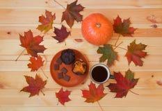 Kubek kawa, jesień liście klonowi, bania i słodka bułeczka na drewnianym stole, obrazy royalty free
