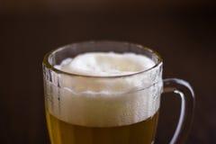 Kubek piwo na drewnianym tle Obrazy Stock